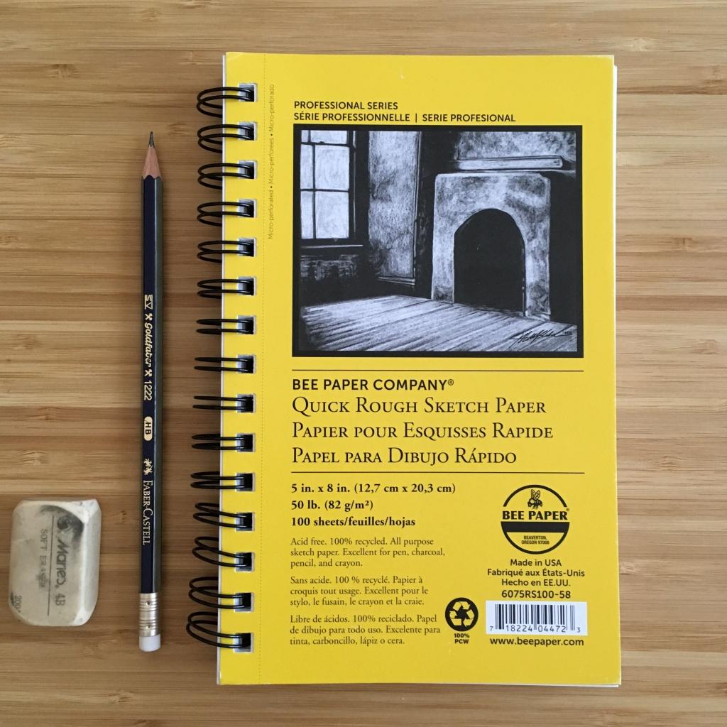 A sketch paper notebook, a graphite pencil, and an eraser.